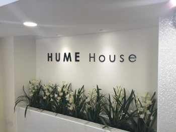 Cut out aluminium lettering, powder coated and illuminated by ceiling mounted spot lighting.
