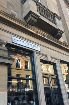 Cast metal plaques with hand decorated raised text and crest in the commercial quarter of Newcastle.